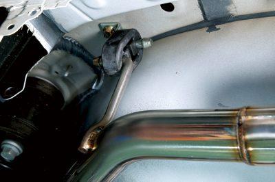 ノーマルマフラーは運転席側のみだが、助手席側マフラーは純正のネジ穴にステーを装着して固定