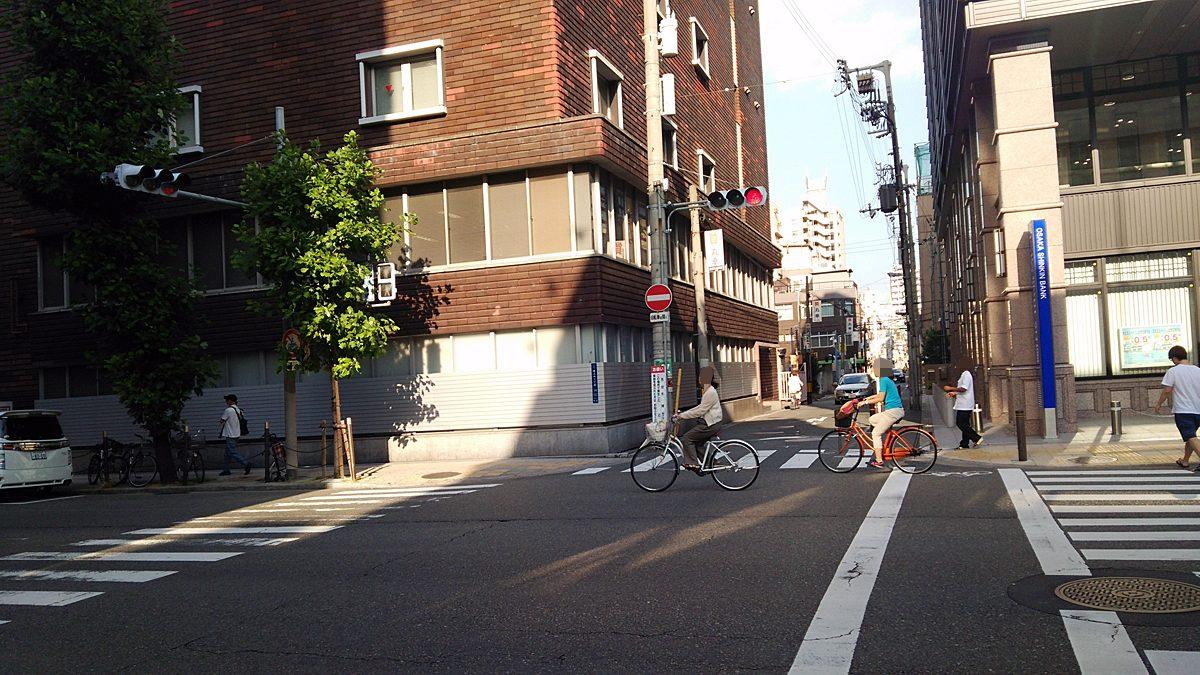 向かってくる方向の道のみが青信号。左右の道路は赤信号ながらも、自転車は信号無視して横断中